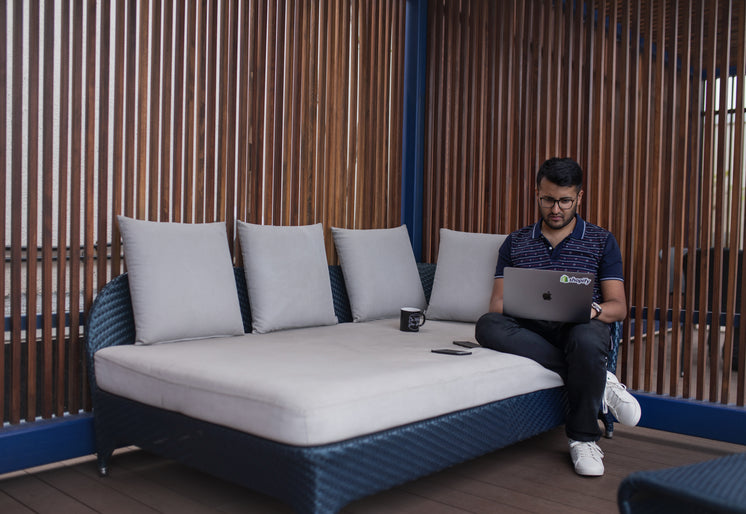 Young Man Working On Patio Couch