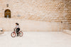 young person riding a bike on stone surface