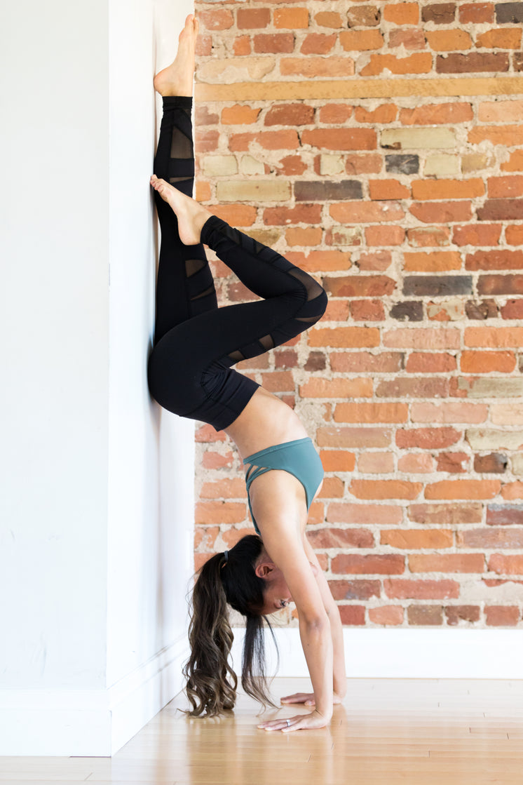 Young Woman Doing Handstand Yoga Pose