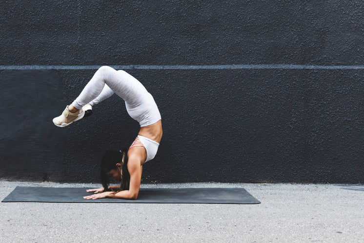 Young Woman Doing Yoga Pose Against Black Wall