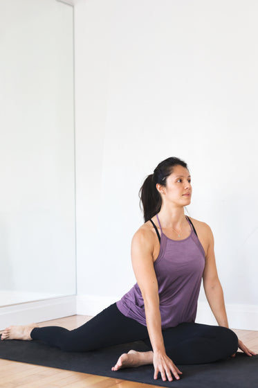 young woman doing yoga pose against white wall