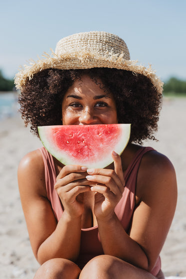 young woman holds watermelon slice on sunny beach