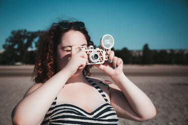 young woman in sunglasses taking photograph on beach