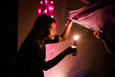 young woman places candle inside lantern
