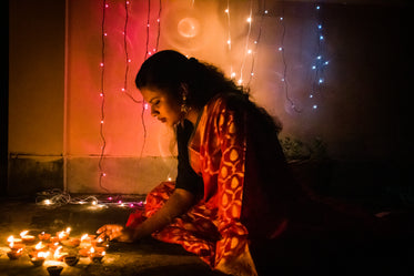 young woman places diwali candles