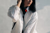 young woman posing in white jacket