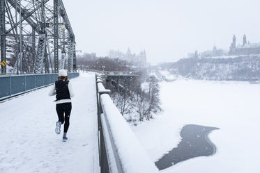 young woman running across a snowy bridge