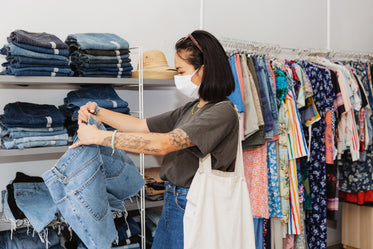 young woman shopping for clothes with face mask on