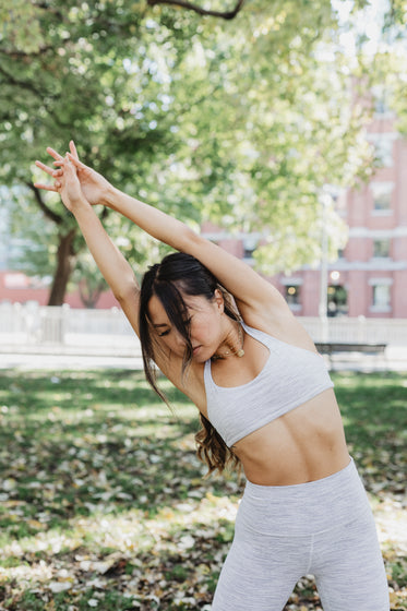 young woman stretching in a park
