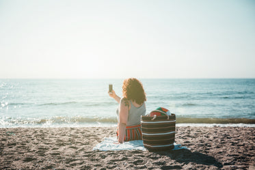 young woman takes selfie while sitting on sunny beach