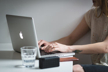 young woman typing macbook