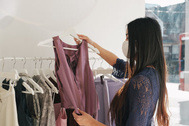 young woman wears mask while clothes shopping